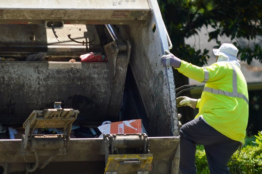 A sanitation worker hangs on to the back of a garbage truck on Tuesday, April 21, 2020, while near Shreveport's South Highland neighborhood.