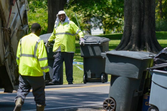 A sanitation worker drags trash bins to the back of a garbage truck on Tuesday, April 21, 2020, while near Shreveport's South Highland neighborhood.