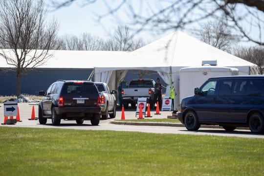 Vehicles wait in line at a drive-up coronavirus test site on Tuesday, April 21, behind the Sanford clinic in Worthington, MN.