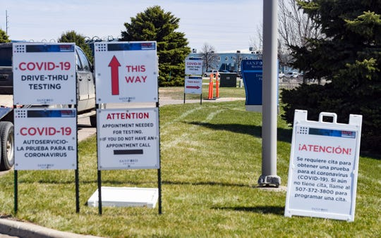 Signs direct vehicles to a drive-up coronavirus test site on Tuesday, April 21, behind the Sanford clinic in Worthington, MN.