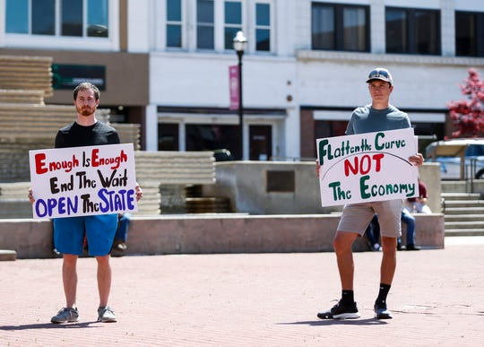 Devin Cannon (left) and Philip Hansen protest on the Park Central Square in Downtown Springfield to urge city officials to end the stay-at-home order on Tuesday, April 21, 2020.