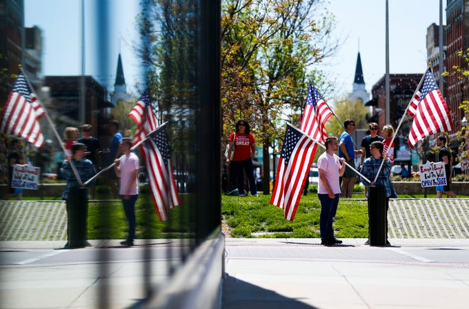 Protesters stand with American flags on the Park Central Square in Downtown Springfield to urge city officials to end the stay-at-home order on Tuesday, April 21, 2020.