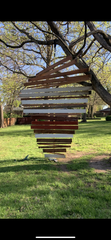 This is a lawn ornament created by the Broekhoven family. It was sourced from found materials on site including boards and a tree swing. It is about 18 feet high.