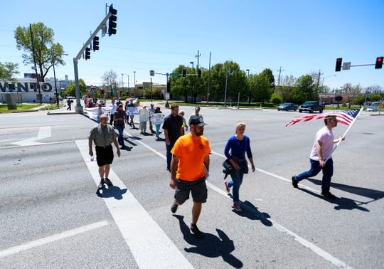 Protesters march from the Park Central Square to Historic City Hall to urge city officials to end the stay-at-home order on Tuesday, April 21, 2020.