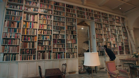 """Adam Weinberger examining a bookshelf in """"The Booksellers."""""""