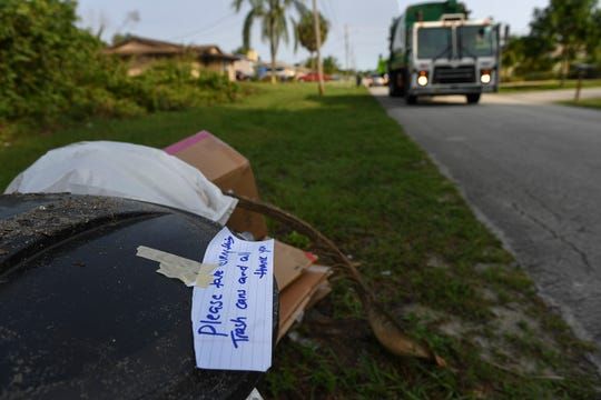 A resident along Southwest Idaho Avenue left a note for the Waste Pro crew to take several old trash cans along with their content during their trash pickup on Tuesday, April 21, 2020, in Port St. Lucie.