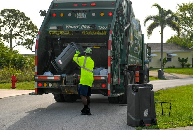 Leroy Green, a Waste Pro garbage collection crewman, photographed working on Tuesday, April 21, 2020, in Port St. Lucie, Florida.