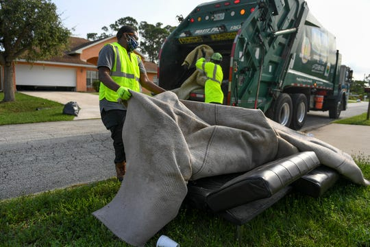 """Martavious Hair (left), and Leroy Green, residential helpers with Waste Pro, wrestle with carpeting laying on top of a couch during their trash pickup along Southwest Goodman Avenue on Tuesday, April 21, 2020, in Port St. Lucie. """"Monday, Tuesday, and Wednesday we normally take our bulk items,"""" Green said. On Thursday, Friday and Saturday they accept lighter weight items, plastic bags and trash cans, """"but now everybody is just putting out what they want to put out and it's uncontrollable."""""""