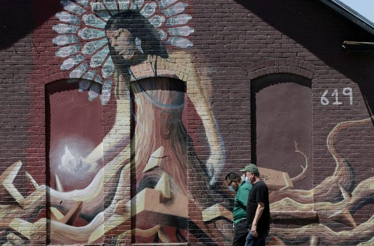 Two men walk past a mural on Oregon Street in downtown El Paso on Tuesday, April, 21, 2020, both wearing masks to protect from coronavirus.