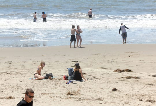 Beach-goers relax near the pier in Ventura on Tuesday, April 21, 2020. The City Council voted to allow limited access to parks, beaches and the pier.
