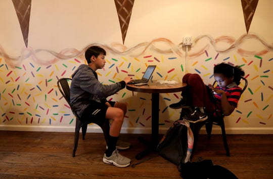 Sebastian Sledge, 13, and his sister Adelaide, 10, do school work in the back of Penny Lick Ice Cream Co., their mother's ice cream shop in Hastings-on-Hudson, April 20, 2020. With schools closed due to the Coronavirus pandemic, the two kids, along with their older sister, Maddie, 16, often come to the shop with their mother and do their eLearning in a back room.