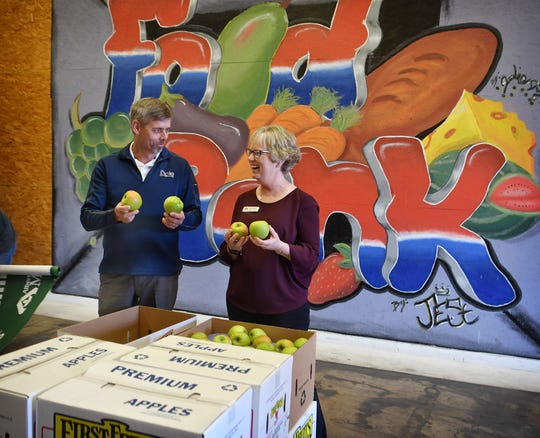 United Market Street produce manager Jeff Little and Wichita Falls Area Food Bank director Kara Nickens look over some of the 5,680 pounds of apples United donate to the WFAFB Tuesday.