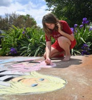 Meagan Perry adds detail to one of the anime characters she drew in sidewalk chalk at her Wichita Falls home.