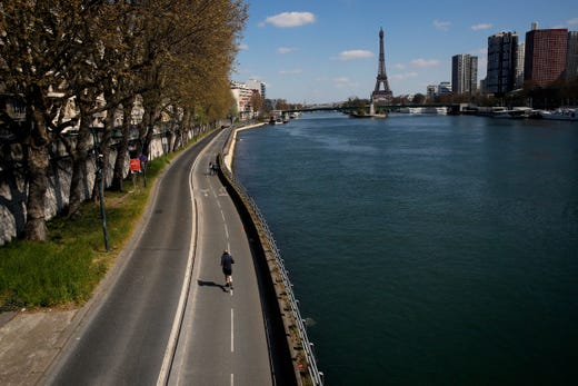 A man jogs on an empty street along the Seine river in Paris on April 4, 2020.