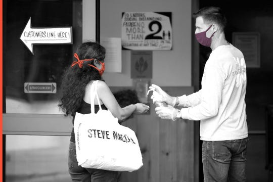 A store associate distributes hand sanitizer to customers as they enter the Trader Joe's store in South Beach on April 14, 2020 in Miami Beach, Florida. The city of Miami Beach put in place an emergency measure requiring all customers and employees at grocery stores, restaurants and pharmacies to wear face coverings to help fight against the COVID-19 pandemic.