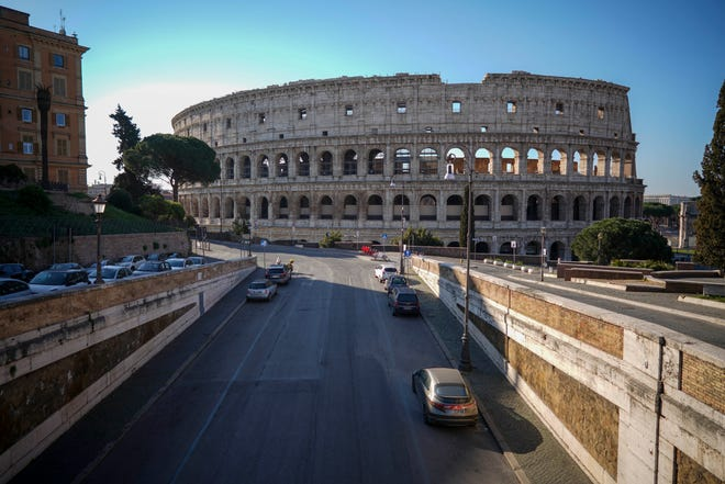 An empty street leads to the ancient Colosseum, in Rome, on March 24, 2020.