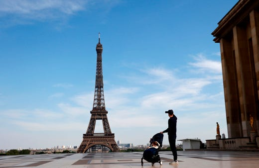 A man takes a picture of the Eiffel Tower on the empty Trocadero esplanade in Paris, on April 20, 2020, on the 35th day of a strict lockdown in France aimed at curbing the spread of the COVID-19 pandemic, caused by the novel coronavirus.