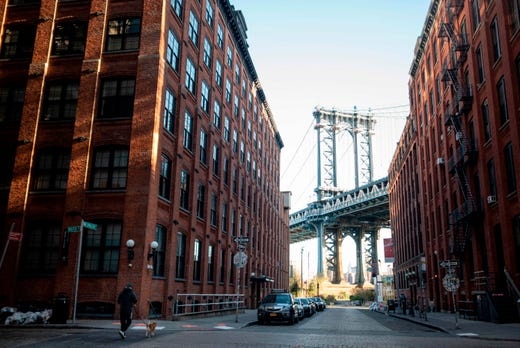 A man walks his dog through the deserted Dumbo neighborhood of Brooklyn in front of the Manhattan Bridge on April 11, 2020 in New York City.