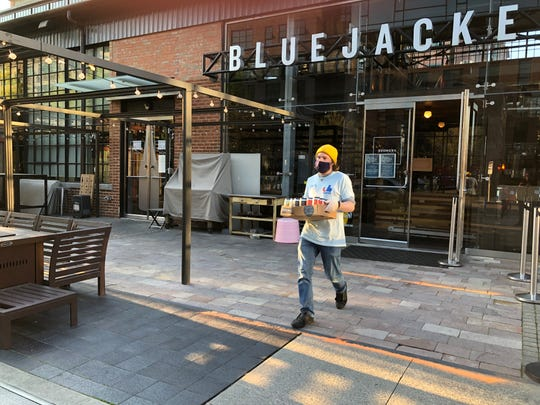 Conor Provost of Bluejacket brewery in Washington, D.C., puts beer in a car. The brewpub now takes beer and food orders online or by phone and will deliver to customers at the curbside, as well as delivering to homes in the area.