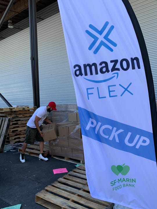 An Amazon Flex driver loads boxes of food at the San Francisco-Marin Food Bank. The company has partnered with food banks nationally to provide free delivery of food to people who must shelter in place during the COVID-19 emergency.