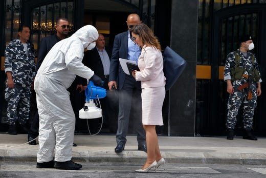 A paramedic sprays Minister of Information Manal Abdul-Samad with disinfectant as she arrives for a parliament meeting, in Beirut, Lebanon, April 21, 2020. Lebanon's parliament began a three-day legislative session Tuesday at a Beirut theater so that legislators can observe social distancing measures due to the coronavirus pandemic, as protests against the country's ruling elite in the crisis-hit country resumed.