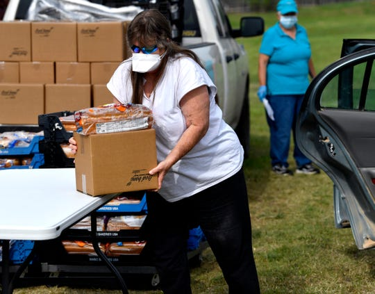 A client takes a package of food during a distribution Wednesday by the Food Bank of West Central Texas at All for One Missions Church.