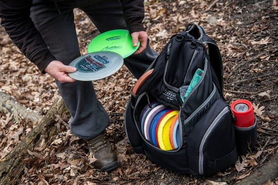 Morgan Dally, 22, plays disc golf while he is off of work due to the COVID-19 pandemic on Wednesday, April 22, 2020 at Leila Arboretum in Battle Creek, Mich.