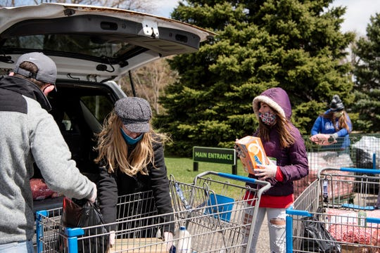 Volunteers distribute food at South Michigan Food Bank in Battle Creek, Mich. on Tuesday, April 21, 2020 as unemployment numbers soar to record highs throughout the COVID-19 pandemic.