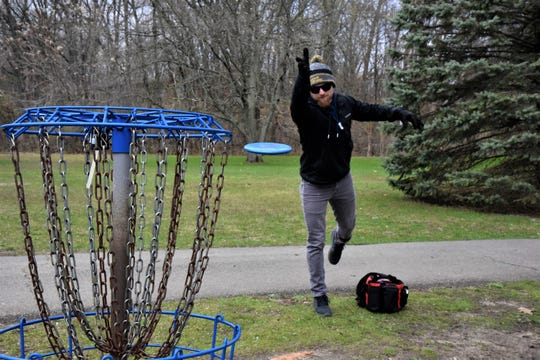 Jesse Mosier, 23, makes a putt on the first hole on the disc golf course at Irving Park in Battle Creek on Wednesday, April 22, 2020.