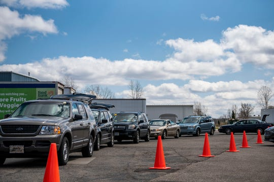 Vehicles form a line to receive food from South Michigan Food Bank in Battle Creek, Mich. on Tuesday, April 21, 2020 as unemployment numbers soar to record highs throughout the COVID-19 pandemic.