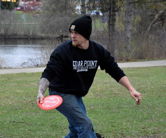 Shane Tenney, 25, tees off on the first hole of the disc golf course at Irving Park in Battle Creek on Wednesday, April 22, 2020.