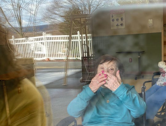 Nina Masucci, 97,  a resident of Ideal Living in Endicott, blows kisses to her children during a weekly window visit.