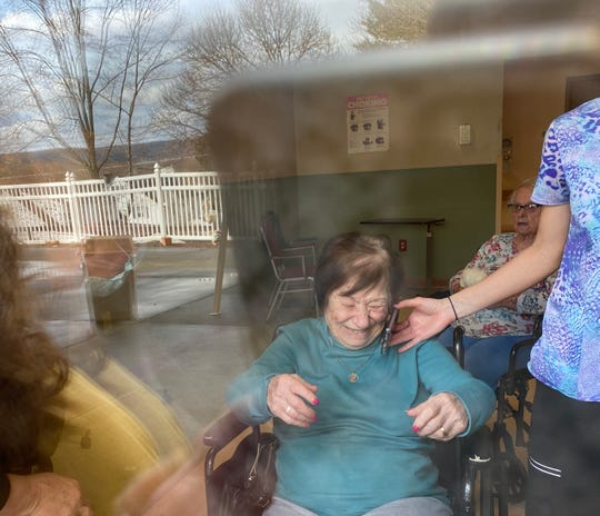 Nina Masucci smiles as she speaks with her daughter over the phone during a window visit at Ideal Living in Endicott.