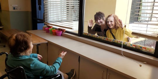 Nina Masucci, a resident of Ideal Living in Endicott, enjoys a window visit with two of her children, Patty Tabeek (left) and Barbara Wahila.