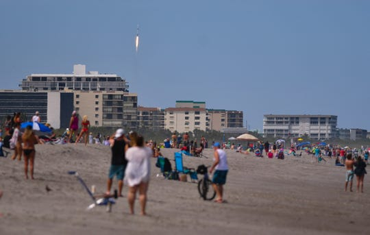 A launch with social distancing: People at Minutemen Causeway watch as SpaceX launches its seventh batch of Starlink communications satellite on April 22. The Falcon 9 rocket lifted off Kennedy Space Center's Pad 39A on the 50th anniversary of Earth Day.
