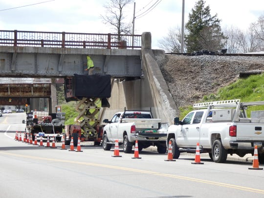 A Norfolk-Southern Railway crew works on the easternmost of three overpasses on East Mansfield Street on Tuesday. The overpass was inspected by the railroad after concrete from the structure fell on the sidewalk below in early March, and additional repairs were scheduled. During Tuesday's Bucyrus City Council meeting, Mayor Jeff Reser said city officials have been assured the crews will keep at least one lane of East Mansfield open at all times while the work continues.