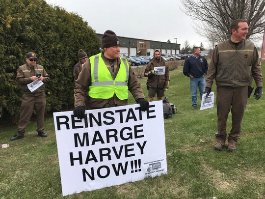 Scott Carpenter holds a sign in support of Marge Harvey at a small rally at the UPS facility in Williston on Wednesday, April 22, 2020.