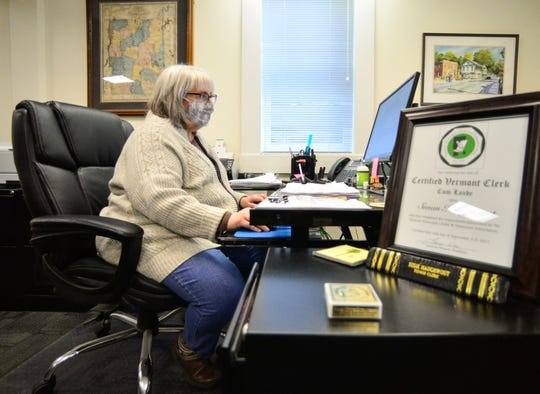 Susie Haughwout, the town clerk for Wilmington, Vt., sits at her computer to work on Tuesday, April 21, 2020. Haughwout opened the office back up for appointments only after Vermont Gov. Phil Scott relaxed some of the restrictions because of the coronavirus.