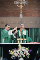 """The Rev. Robert Little, left, and the Rev. Dallas St. Peter complete the Eucharistic prayer at a service at St. Mark Parish in Burlington in 2018. """"Our faith is the only thing we have to fall back to that is supporting and consoling and reminding us that we are not meant for this life alone,"""" St. Peter said."""