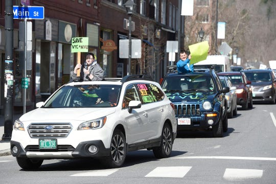 A long line of vehicles parade through downtown Montpelier, Vt., honking, waving and holding signs for more than an hour Monday, April 20, 2020, to protest a proposed plan to shutter three campuses in the Vermont state college system due to coronavirus.