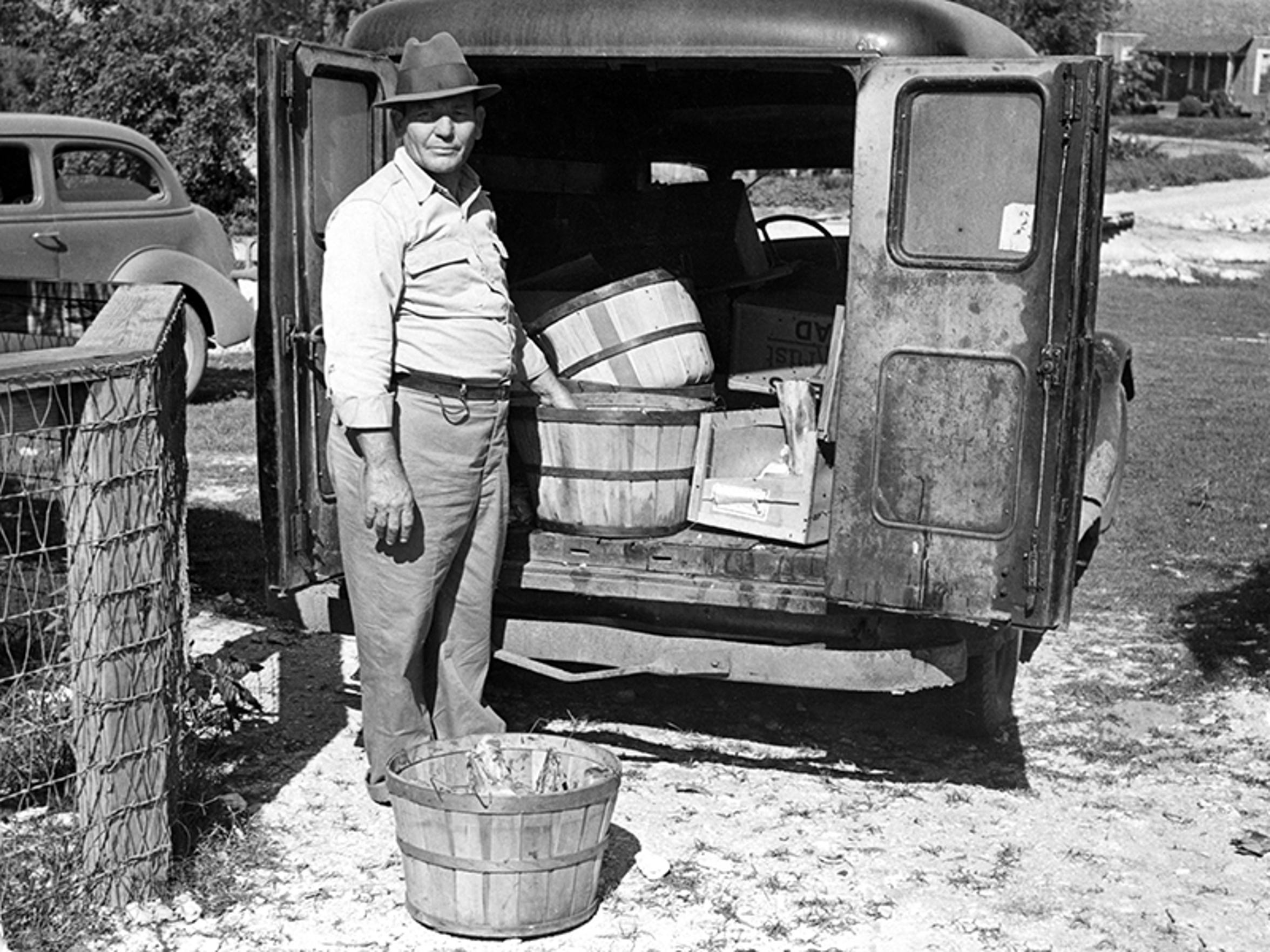"""Ricardo """"Dick"""" Flores was the zookeeper for Corpus Christi's zoo from 1936 to 1946. He was paid $125 a month. Here he stands with his truck and baskets of food for the animals in September 1938, when the zoo was located in Ben Garza Park. Photo by Doc McGregor, courtesy of the Corpus Christi Museum of Science and History."""