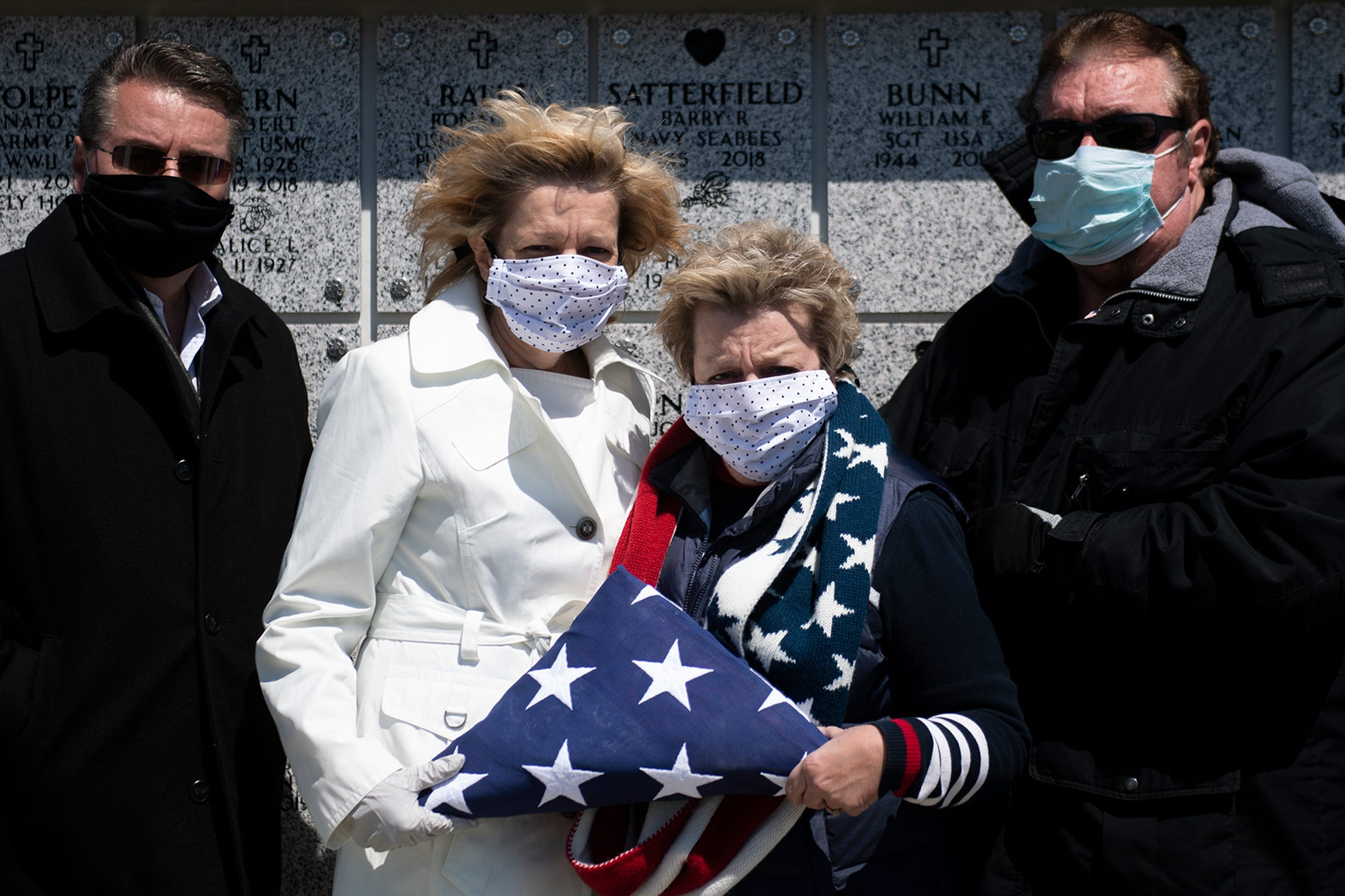 "Siblings Kirk Taggart, from left, Lisa Scanlon, Lynn Wright and Scott Taggart wear masks during a funeral service for their father Herman Taggart Wednesday, April 22, 2020 at Gloucester County Veterans Cemetery in Williamstown, N.J. Herman Taggart, 92, was a Navy veteran who served in World War II. ""The Taggart family is known for being fun loving,"" said Scott Taggart while discussing the inability to celebrate their father's life together. ""We'd normally be having a few cocktails at this point,"" he said."