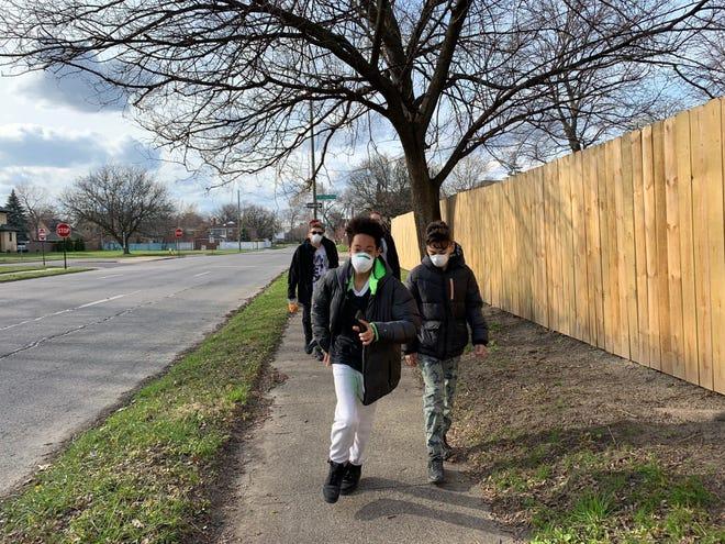 jessica Care moore's son King Thomas Moore, 13, runs down a city sidewalk.