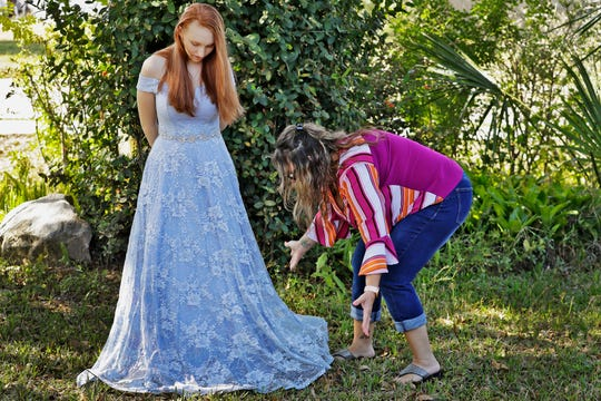 In this April 3, 2020 photo, Annette Reynolds, right, puts the finishing touches on her daughter Amanda's prom gown as she poses for a photo outside their home in Largo, Fla.