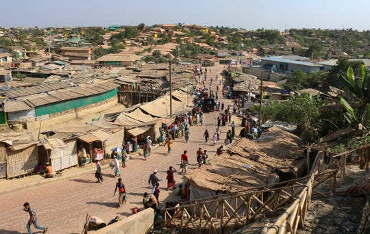 In this April 12, 2020 photograph, Rohingya refugees walk through one of the arterial roads at the Kutupalong refugee camp in Cox's Bazar, Bangladesh.