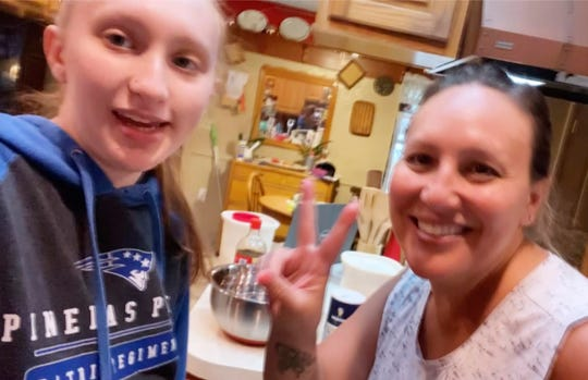 In this April 5, 2020, selfie provided by Amanda Reynolds, she and her mother Annette Reynolds pose for the photo at their home in Largo, Fla. The Florida teen recently marked her 18th birthday at home, obeying state guidelines and social-distancing rules, by making a cake with her mother and not celebrating with friends as she had planned.