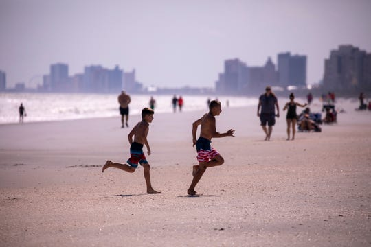Groups of residents enjoy the beach in the Arcadian Shores section of Horry County, S.C., which was opened on Tuesday, April 21, 2020 despite the City of Myrtle Beach choosing not to open public access.
