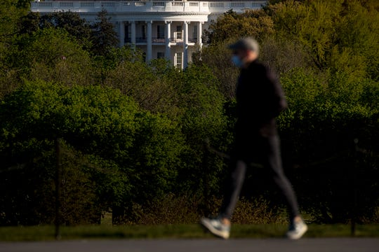The White House is visible as a man wearing a mask makes his way across the National Mall, Wednesday in Washington. Amid pockets of attention-grabbing protests, a new survey finds Americans remain overwhelming in favor of stay-at-home orders and other efforts to slow the spread of coronavirus.