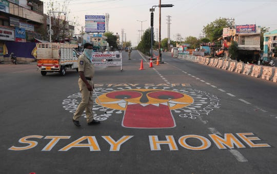 An Indian policeman walks past an art work displayed on road urging people to stay home during lockdown to prevent the spread of new coronavirus in Hyderabad, India, Wednesday, April 22, 2020. India has reported nearly 20,000 confirmed cases of COVID-19 and over 600 deaths.