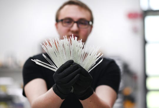 Jason Spurlock, process control engineer with Envision TEC, holds many flexible nasal swabs made with 3D printers at the Dearborn plant.